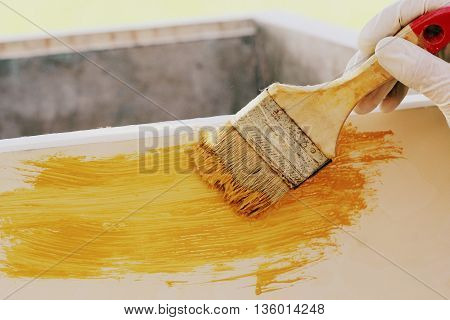 Painting wood furniture with yellow paint .