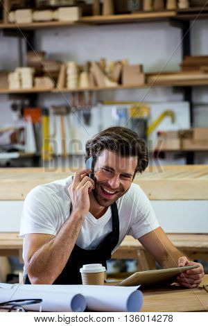 Carpenter calling someone and holding his tablet in a dusty workshop