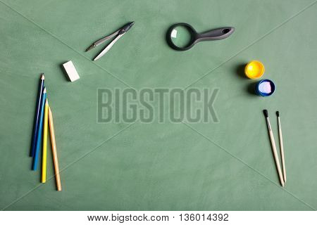 Back to school concept. Compass magnifying glass brush eraser on the black chalkboard. You can put your text or image on the center