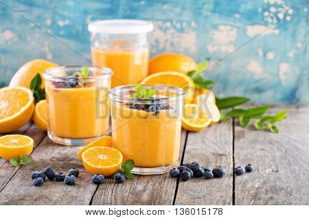 Orange and mango healthy smoothie served with granola and berries