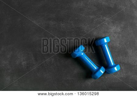 Two blue dumbbells on a black chalkboard