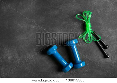 Two blue dumbbells and jumping-rope on a black chalkboard