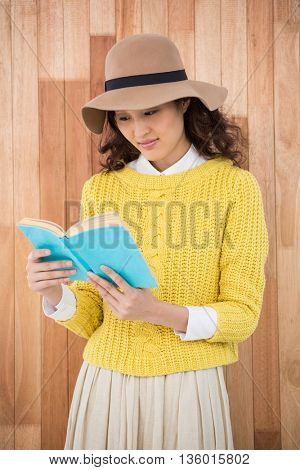 Hipster reading a book on wooden background