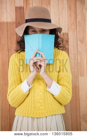Hipster holding a book on wooden background