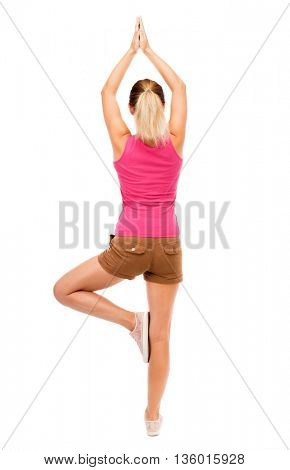 Back view of the girl standing in front a warm up exercise.  Rear view people collection.  backside view person.  Isolated over white background. girl in brown shorts and a pink t-shirt doing yoga