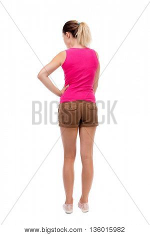 back view of standing young beautiful  woman.  Rear view people collection.  backside view of person.  Blonde girl in shorts and a pink blouse is resting his hand in his right side. and looking up.