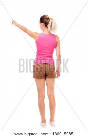 Back view of  pointing woman. beautiful girl. Rear view people collection.  backside view of person.  Isolated over white background. The girl in brown shorts and a pink tank top is pointing to right