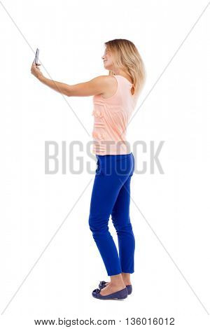 back view standing young beautiful woman and using mobile phone. Rear view people collection. backside view person. Isolated over white background. Blonde in blue pants makes self smartphone on white