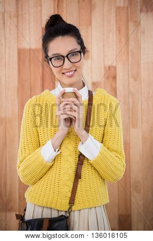 Hipster holding a cup of coffee on wooden background