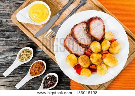 Roasted new potatoes with sea salt red bell pepper and meat cutting into slices on a white dish with mustard in a gravy boat on a wooden background close-up view from above