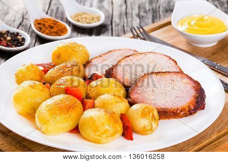 Oven Baked new potatoes with sea salt red bell pepper and meat tenderloin cutting into slices a white dish with sauce in a gravy boat on a wooden background close-up view from above