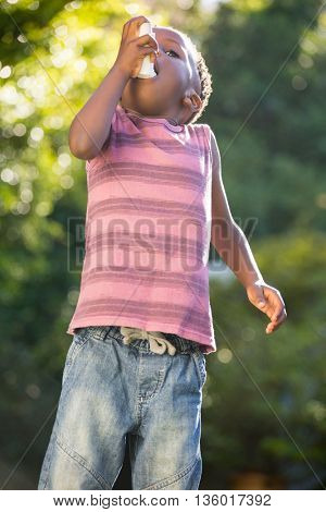 Boy using a asthma inhalator in a park