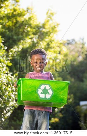 Boy carrying a recycle trash in a park