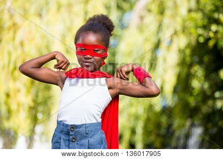 Cute mixed-race girl wearing a fancy dress and showing her biceps on a park