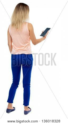 back view of standing young beautiful  girl with tablet computer in the hands of. girl  watching. Isolated over white background. Blonde girl in trousers is left side and looking at tablet computer.