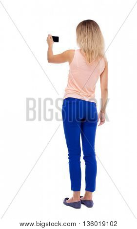 back view of standing young beautiful  woman  and using a mobile phone. Rear view people collection.  Isolated over white background. Blonde in blue pants makes video holding the camera with one hand.