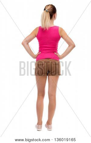 back view of standing young beautiful  woman.  girl  watching. Rear view people collection.  backside view of person. Isolated over white background. Blonde in brown shorts standing with hands on hips