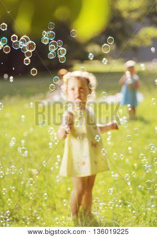 Little girl blowing soap bubbles on a summer meadow