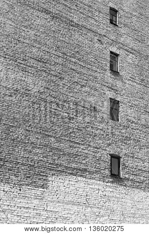 old big brick wall with windows for the textured vintage background of monochrome tone
