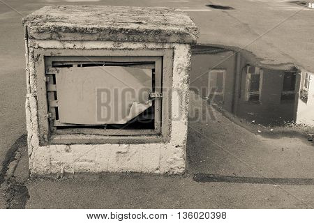 old construction for ventilation in the yard against a puddle with reflection of a fragment of the house of monochrome tone of beige color