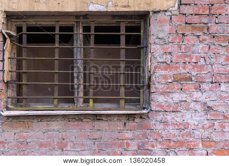 old window closeup with a rusty lattice on an ancient brick wall and a blank space