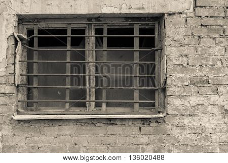 old window closeup with a rusty lattice on an ancient brick wall of beige tone and a blank space