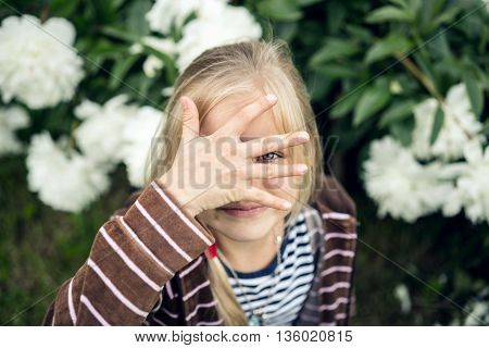 Summer. Beautiful blond girl hiding behind his hand.