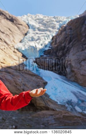 Hand with ice and Briksdal glacier - Norway - nature background