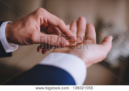 Two wedding rings in a hand of the groom.