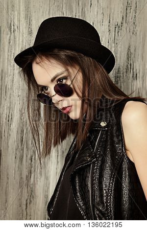 Fashion shot of a modern brunette girl with beautiful big brown eyes wearing black leather jacket. Beauty, fashion. Youth generation.