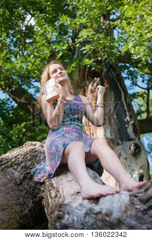 Teenager girl reads a book sitting on a tree in the forest