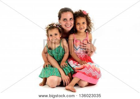 Mother and two mulatto daughter from interracial marriage or adoption. Children are sitting in her mothers lap looking at the camera. Isolated on white background.