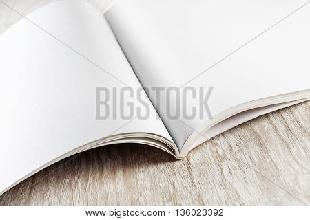 Close-up of blank opened book on light wooden background. Blank mock-up for your design. Photo of blank booklet.