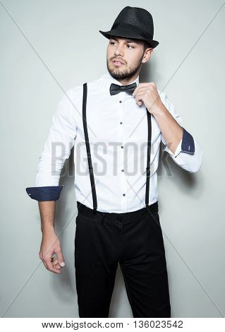 handsome young man in white dress shirt wearing hat, bow tie and suspenders