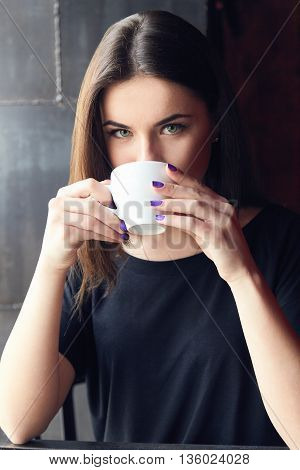 Young beautiful girl drinking tea in cafe holding cup both hands and thoughtfully looking at camera. Girl enjoying her leisure time alone in coffee shop cafe. Girl with green eyes in black t-shirt.