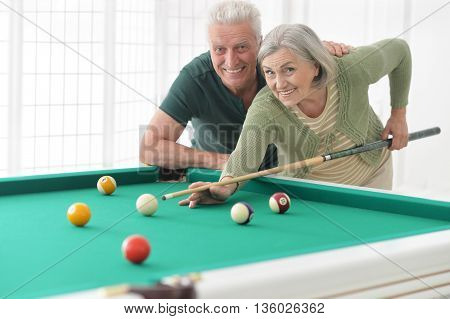 Amusing old couple on vacation playing billiard