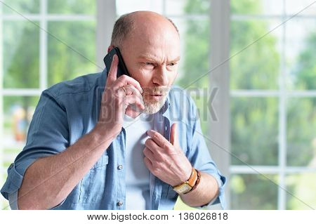 Portrait of an elderly man with phone at home