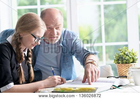 portrait of happy grandfather and little granddaughter doing homework