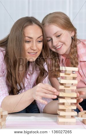 happy mother and daughter  at the table playing board game