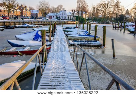 Snowy wooden jetty to the boats in the ice of the small harbor of a Dutch village. It is winter now.