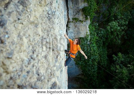 male rock climber. rock climber climbs on a rocky wall. a man hanging by one hand and resting