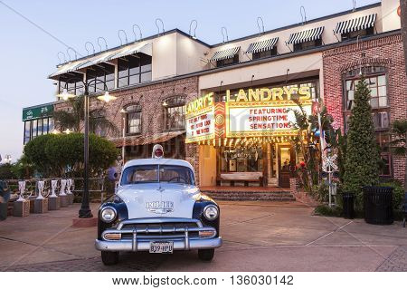 KEMAH TX USA - APR 14 2016: 1952 Chevrolet Styleline Deluxe historic police car and Landry's seafood restaurant at the Kemah Boardwalk. Texas United States