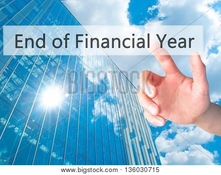 End Of Financial Year - Hand Pressing A Button On Blurred Background Concept On Visual Screen.