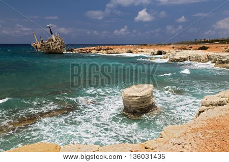 maritime landscape - boat shipwrecked near the rocky shore - turquoise sea with waves on background of cloudy sky. Cliffs in water. The Mediterranean coast near Paphos Cyprus