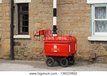 KIRKBY-IN-ASHFIELD ENGLAND - JUNE 27: A Royal Mail high capacity trolley chained to a post. In Kirkby In Ashfield Nottinghamshire England. On 27th June 2016.