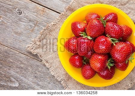 Yellow plate with strawberries on piece of sackcloth
