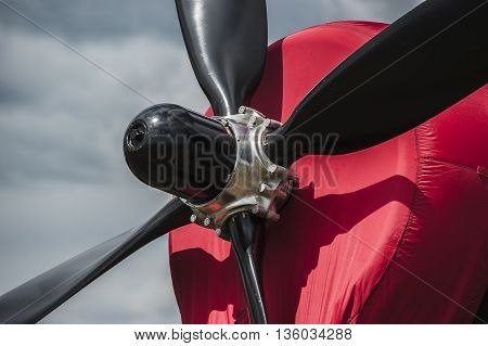 Propeller and engine of old airplane against cloudy sky