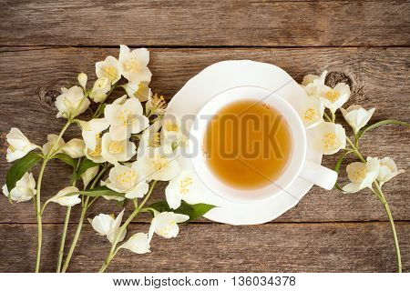 Top view of teacup and blooming flowers on wooden background