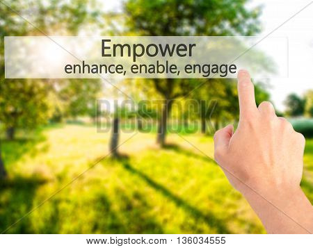 Empower Enhance, Enable, Engage - Hand Pressing A Button On Blurred Background Concept On Visual Scr