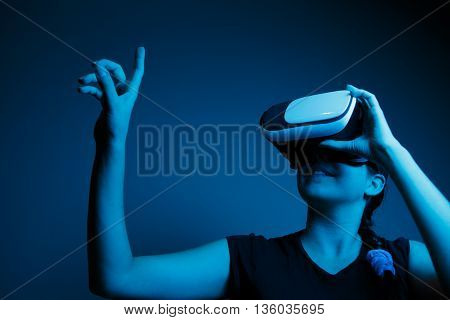 Woman with glasses of virtual reality, VR glasses concept. Toned image with blue
